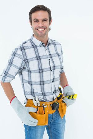 spirit level: Portrait of confident technician holding spirit level over white background