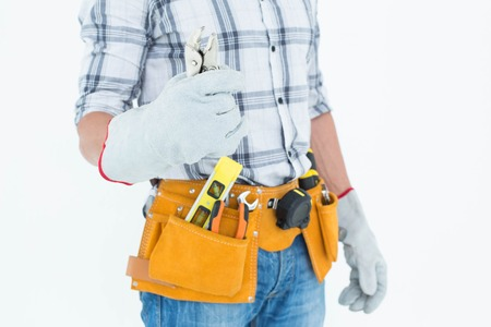 waist belt: Cropped image of technician with tool belt around waist holding pliers over white background