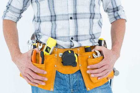 waist belt: Cropped image of technician with tool belt around waist against white background