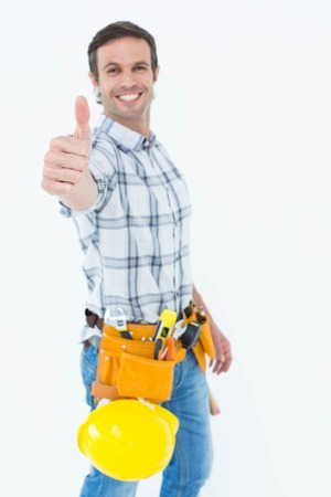 Portrait of confident technician gesturing thumbs up over white background photo