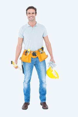 hardhat: Portrait of happy repairman holding spirit level and hardhat over white background Stock Photo