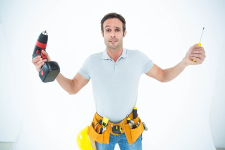confused man: Portrait of confused technician holding screwdriver and drill machine over white background