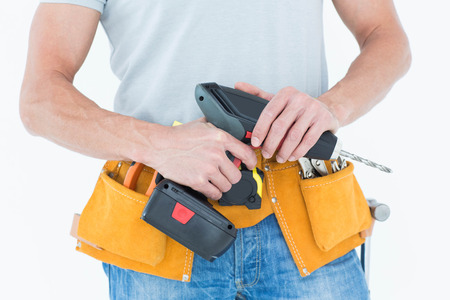 portability: Cropped image of repairman holding handheld drill over white background Stock Photo