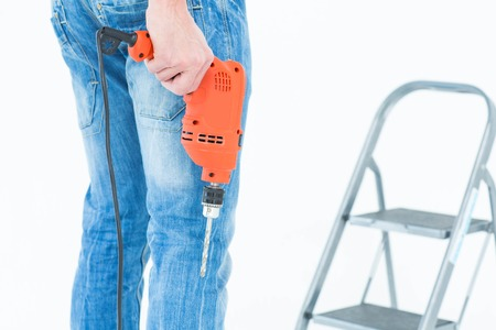 step ladder: Cropped image of worker holding drill in front of step ladder over white background