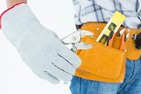 waist belt: Cropped image of technician with tool belt around waist using pliers over white background