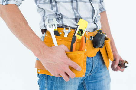 tool belt: Cropped image of technician with tool belt around waist against white background
