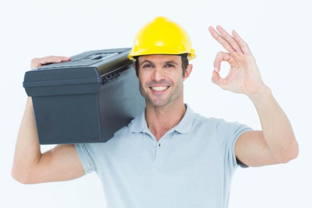Portrait of happy worker carrying tool box on shoulder while gesturing OK sign over white background photo