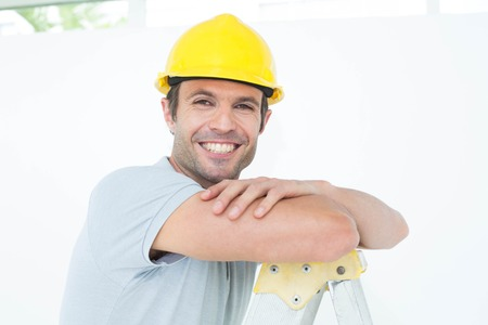 step ladder: Portrait of happy technician leaning on step ladder over white background Stock Photo