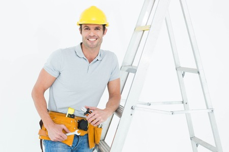 step ladder: Portrait of happy worker holding tools while leaning on step ladder