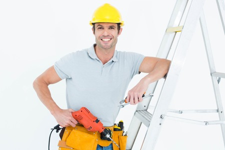 step ladder: Portrait of confident technician holding drill machine while leaning on step ladder