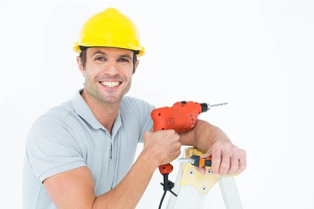 step ladder: Portrait of happy technician holding drill machine while leaning on step ladder