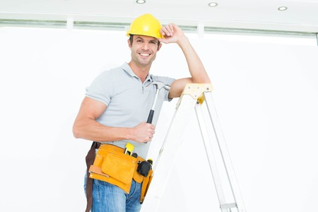 step ladder: Portrait of happy technician holding hammer while wearing hard hat on step ladder Stock Photo
