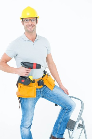 Portrait of confident worker holding drill machine on step ladder over white background photo