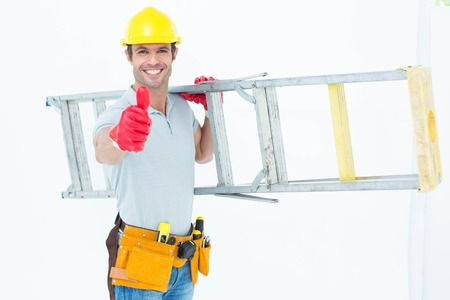 step ladder: Portrait of confident worker carrying step ladder while showing thumbs up over white background