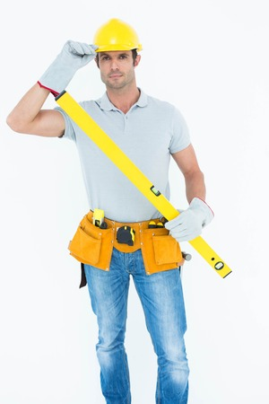 spirit level: Portrait of confident carpenter holding spirit level while wearing hard hat over white background Stock Photo