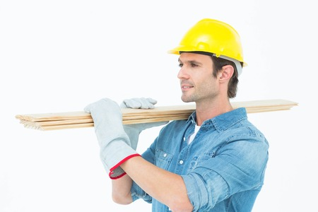 Handsome carpenter carrying wooden planks over white background photo