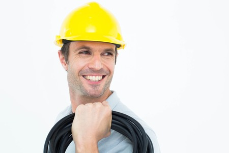 carrying: Handsome electrician carrying wires over white background Stock Photo