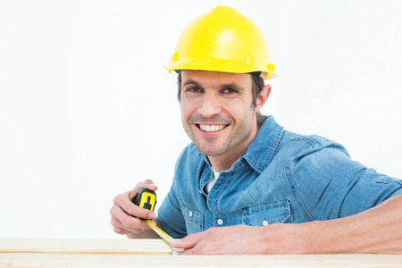 Portrait of happy male carpenter using measue tape over white background photo
