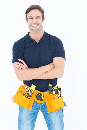Portrait of confident man with tool belt around waist standing arms crossed over white background