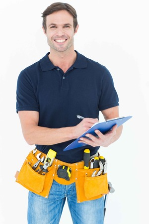 over white background: Portrait of handsome carpenter writing on clipboard over white background