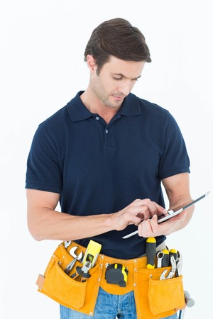 Handsome handyman using digital table over white background