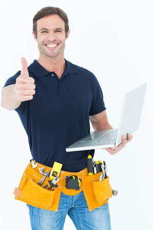 Portrait of worker holding laptop while gesturing thumbs up over white background