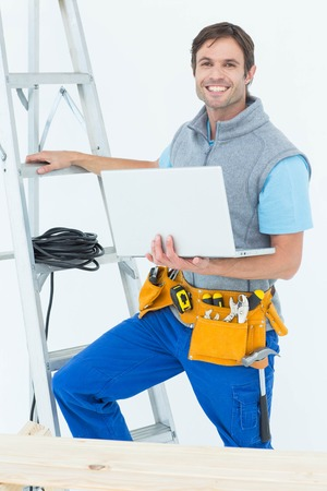 step ladder: Portrait of confident electrician holding laptop by step ladder over white background