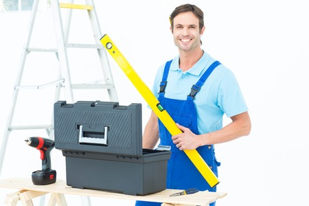 Portrait of happy carpenter holding spirit level at table over white background photo