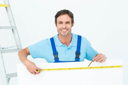 bill board: Portrait of happy carpenter measuring blank bill board over white background