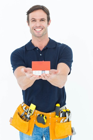model home: Portrait of happy male architect holding model home over white background