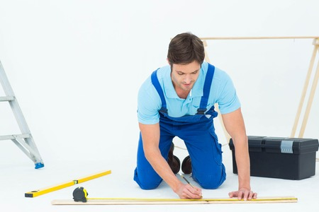 Handsome worker marking on wood while measuring over white background photo