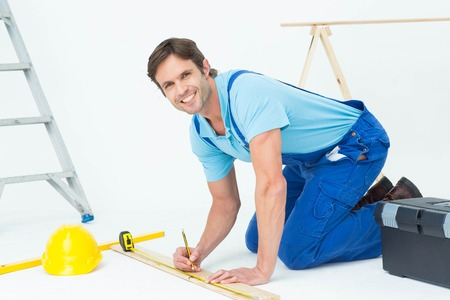 Portrait of confident worker marking on wood while measuring over white background photo