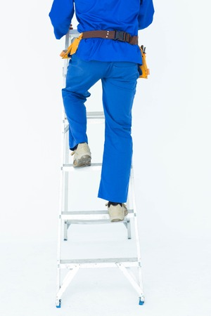 step ladder: Low section of carpenter climbing step ladder over white background