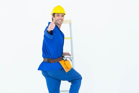 climb job ladder: Portrait of repairman gesturing thumbs up while climbing step ladder over white background