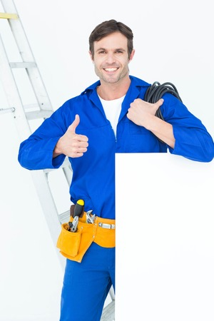 bill board: Portrait of electrician with wire and bill board gesturing thumbs up over white background