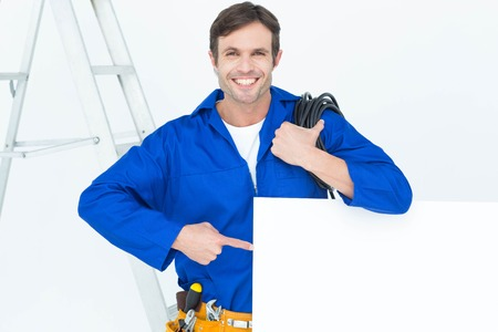 bill board: Portrait of handsome electrician with wire pointing at bill board over white background Stock Photo