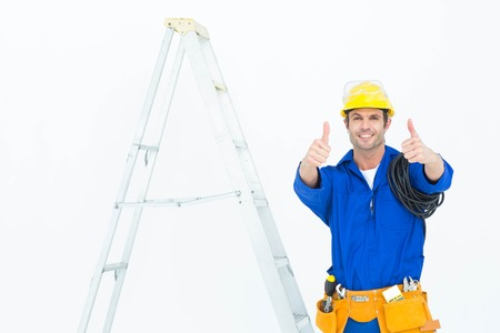 ladder: Portrait of happy electrician gesturing thumbs up while standing by ladder over white background Stock Photo