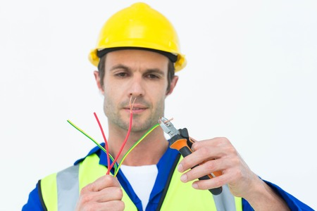Close-up of handsome electrician cutting wire with pliers over white background photo