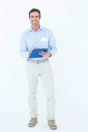 Portrait of confident businessman holding clipboard over white background photo