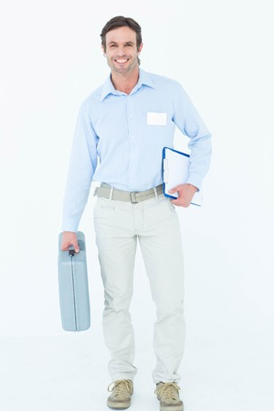 Portrait of confident supervisor carrying tool box and clipboard over white background photo