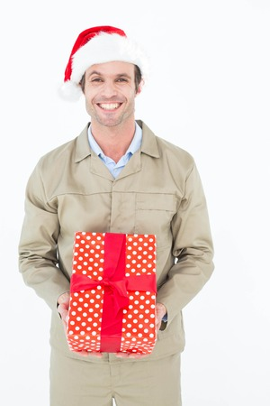 wearing santa hat: Portrait of happy delivery man wearing Santa hat while holding gift on white background Stock Photo