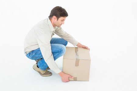 out of the box: Delivery man crouching while picking cardboard box against white background Stock Photo