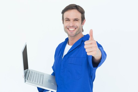 looking up: Portrait of handsome mechanic holding laptop while showing thumbs up over white background Stock Photo