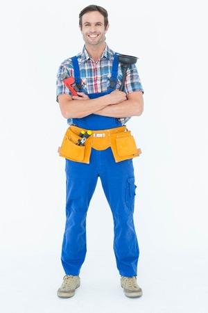 plumber: Full length portrait of confident plumber holding monkey wrench and plunger over white background Stock Photo