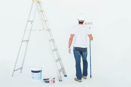 redecorating: Rear view of man with paint roller standing by ladder over white background