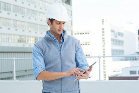 usando computadora: Arquitecto de sexo masculino que usa la tableta digital de fuera del edificio