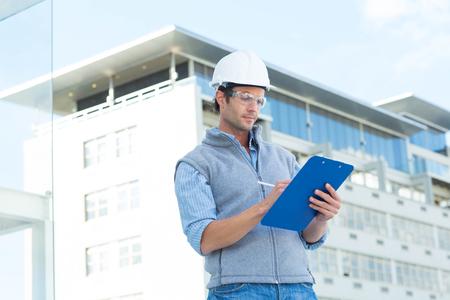 arquitecto: Arquitecto de sexo masculino en la escritura fuera del edificio portapapeles