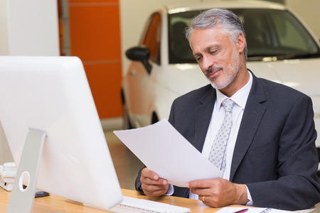 Businessman reading document at office desk at new car showroom