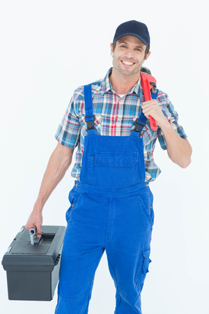 tool box: Portrait of plumber with monkey wrench and tool box over white background