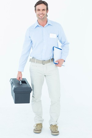 Portrait of happy supervisor carrying tool box and clipboard over white background photo